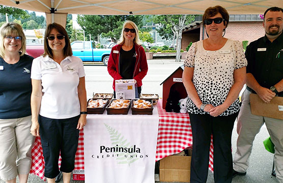 Peninsula Employees under a tent at a community event.
