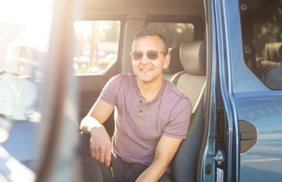 Smiling man in the front seat of a car