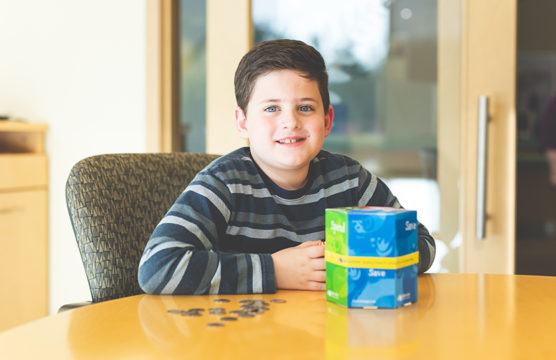 Smiling boy with change on the desk in front of him
