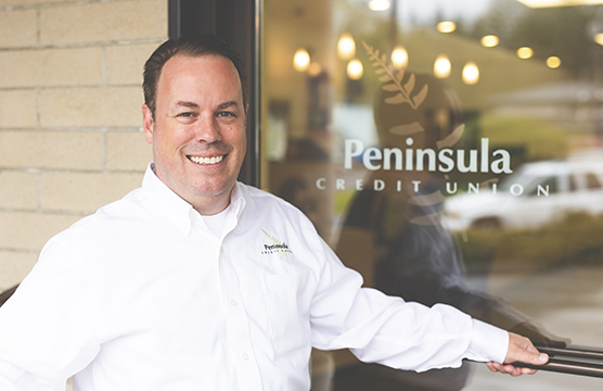 Man smiling in front of a Peninsula sign